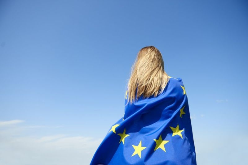 Rear view of young woman covered with European Union Flag