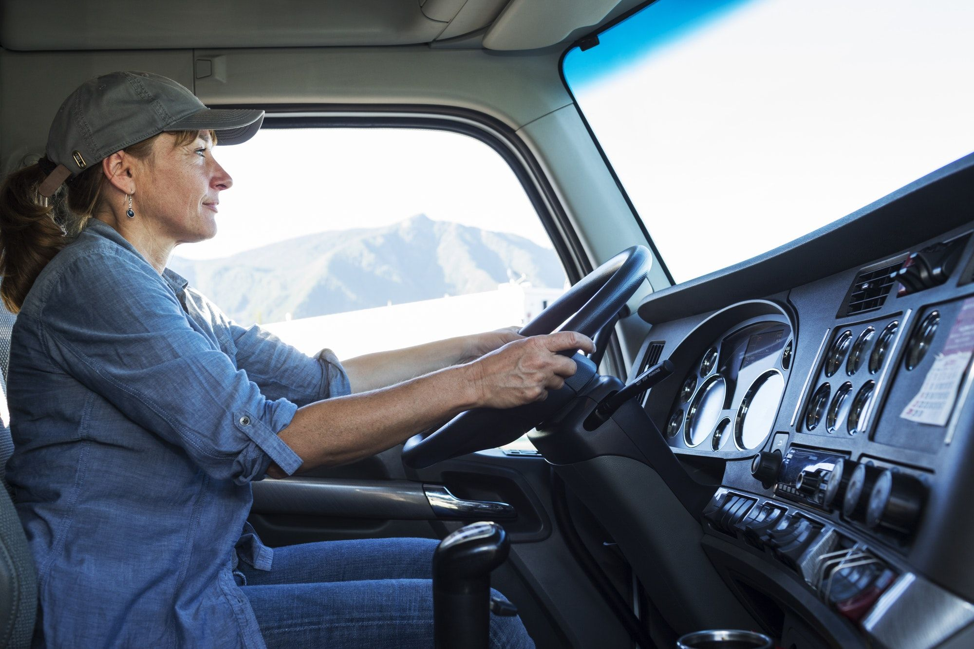 Caucasian woman truck driver in the cab of her commercial truck at a truck stop