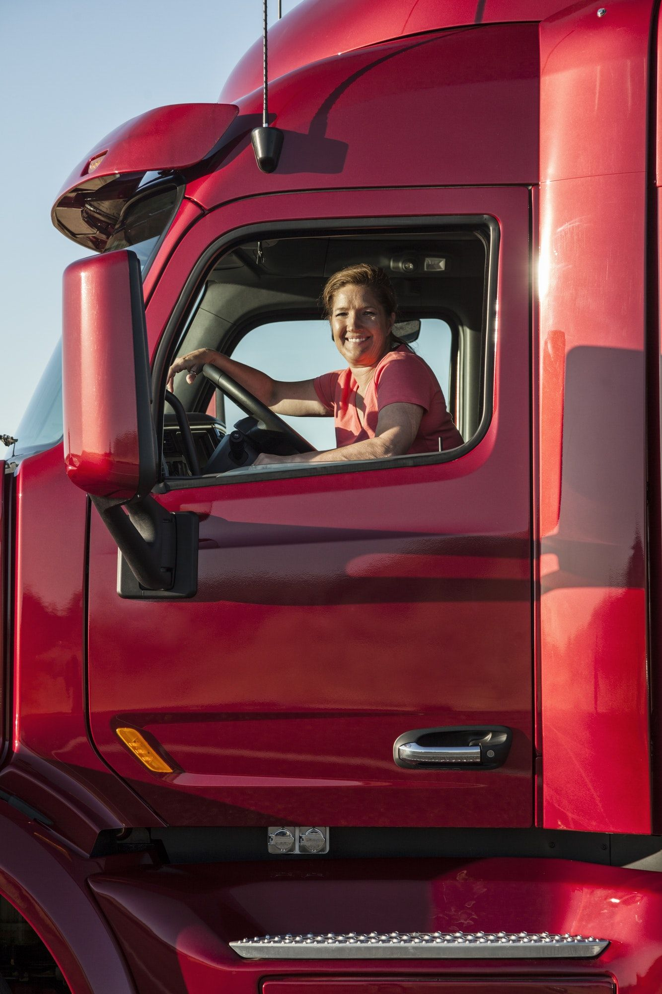 Portrait of a Caucasian woman driver and her commercial truck.