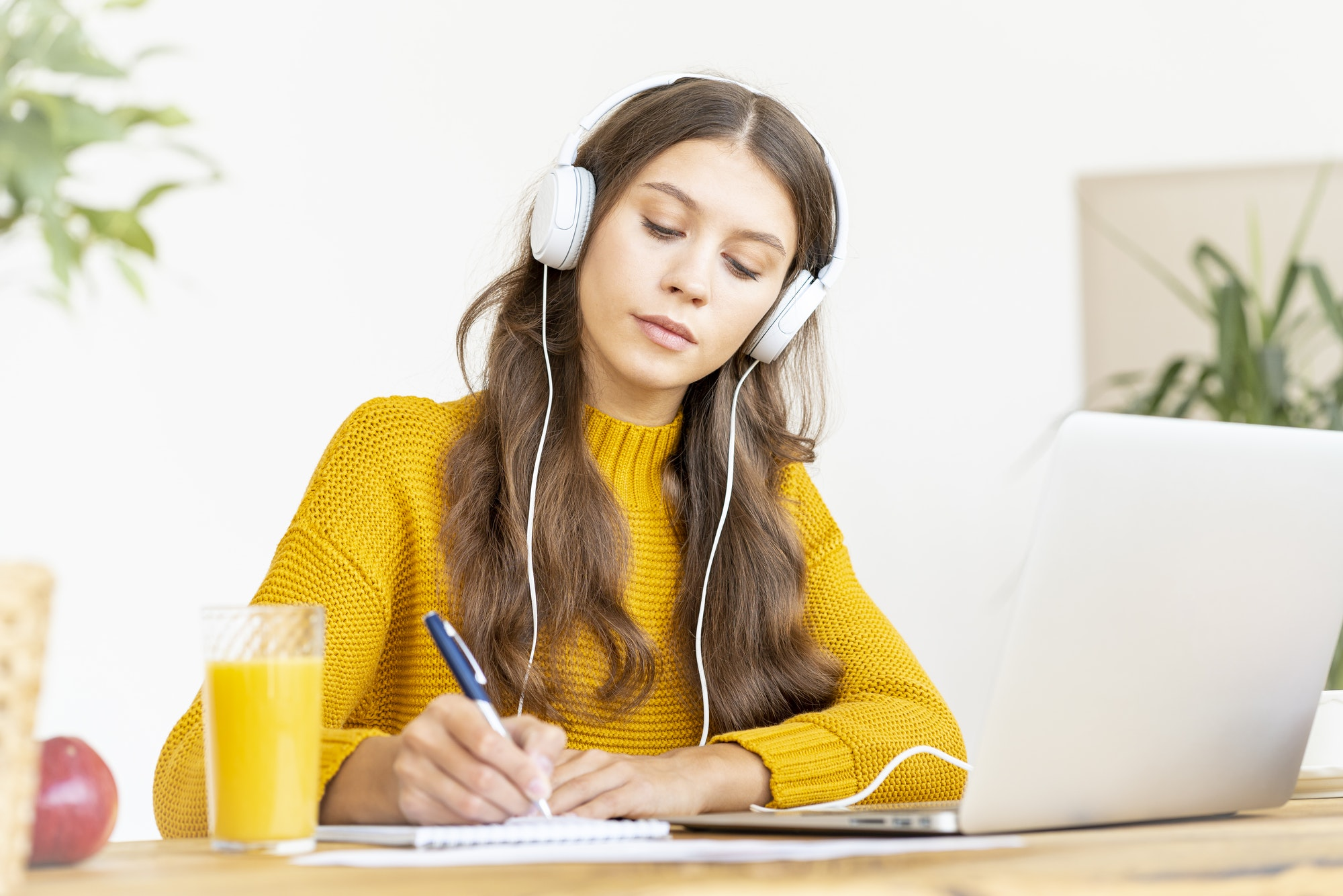 Happy female in wireless headphones studying online course, using pc and writing in notepad